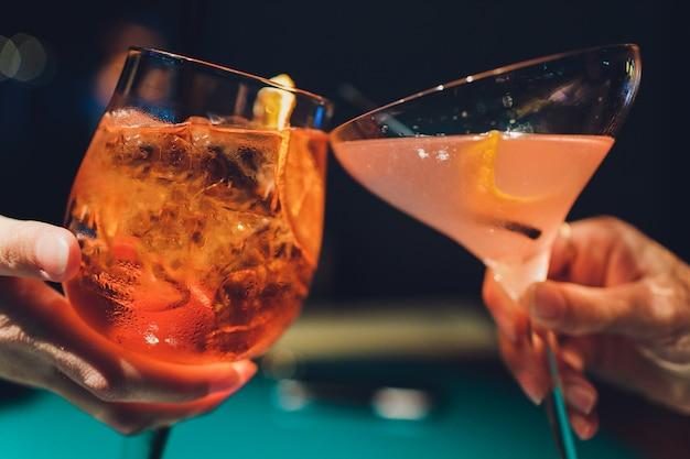 Hände des mannes und der frau, die mit gläsern rosa champagner zujubeln. Premium Fotos