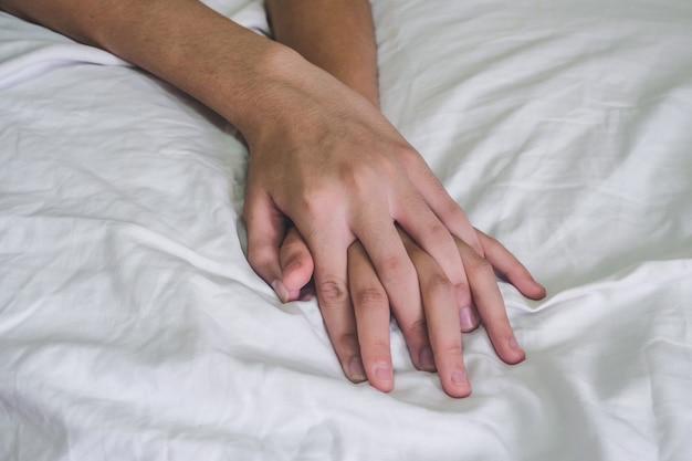 Hände des paarliebhaberssex auf dem bett, konzept über liebe, sex und lebensstil. Premium Fotos