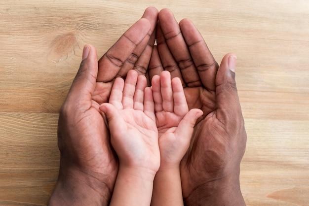 Hände des vaters und des kindes auf holztisch Kostenlose Fotos