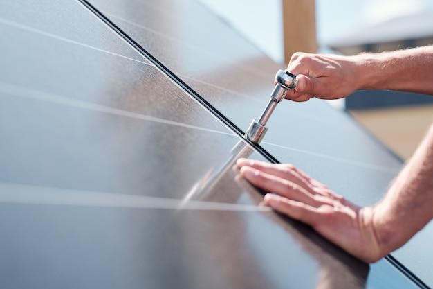 Hände des zeitgenössischen meisters mit schraubenverstellung oder installation von sonnenkollektoren auf dem dach des hauses Premium Fotos