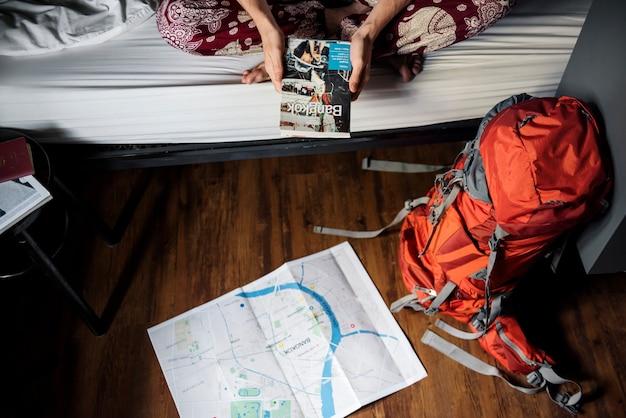 Hände, die bangkok thailand-reiseführerbuch mit karte auf dem boden halten Kostenlose Fotos
