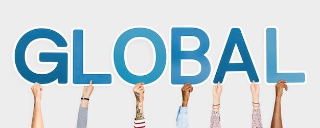 Hände, die blaue buchstaben bilden das wort global halten Kostenlose Fotos