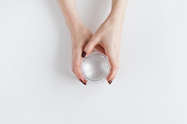 Hände, die ein glas trinkwasser halten. Premium Fotos