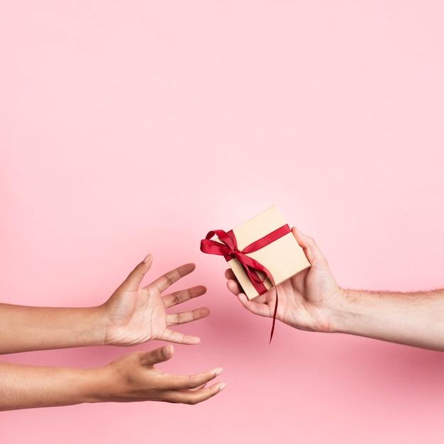 Hände, die ein kleines eingewickeltes geschenk mit band empfangen Kostenlose Fotos