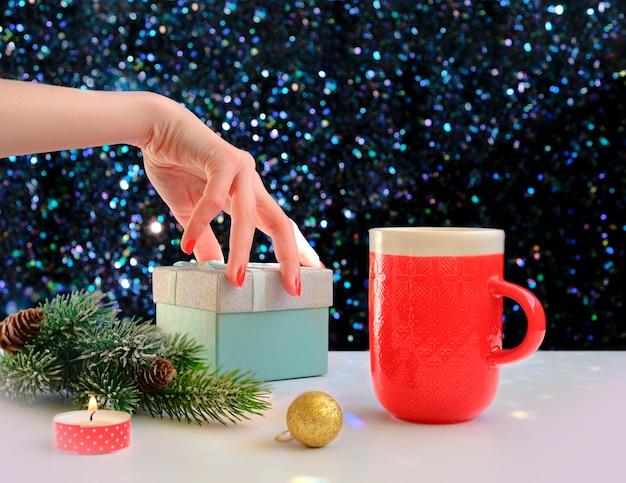 Hände, die eine kaffeetasse auf einem weihnachtshintergrund halten. sicht von oben. weibliche hände, die kaffeetasse halten. weihnachtsgeschenkboxen und schneetannenbaum über holztisch. Premium Fotos