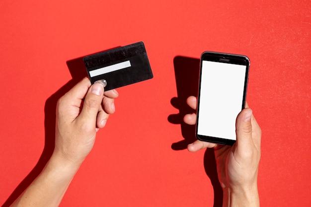 Hände, die eine kreditkarte und einen telefonspott hochhalten Kostenlose Fotos