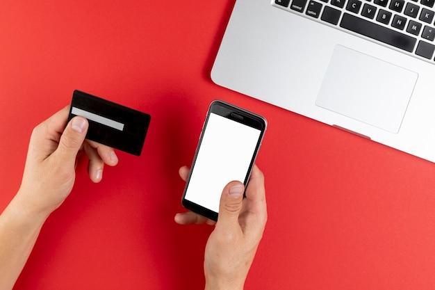 Hände, die eine schwarze karte und einen telefonspott hochhalten Kostenlose Fotos