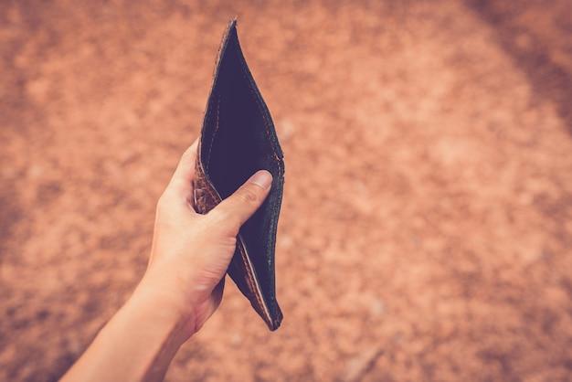 Hände, die einen geldbeutel ohne geld halten. Premium Fotos