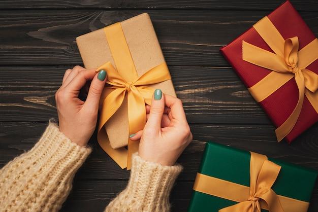 Hände, die goldenes farbband auf geschenk binden Kostenlose Fotos