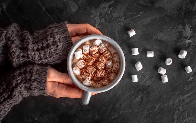 Hände, die heiße schokolade mit eibischen und kakaopulver halten Kostenlose Fotos