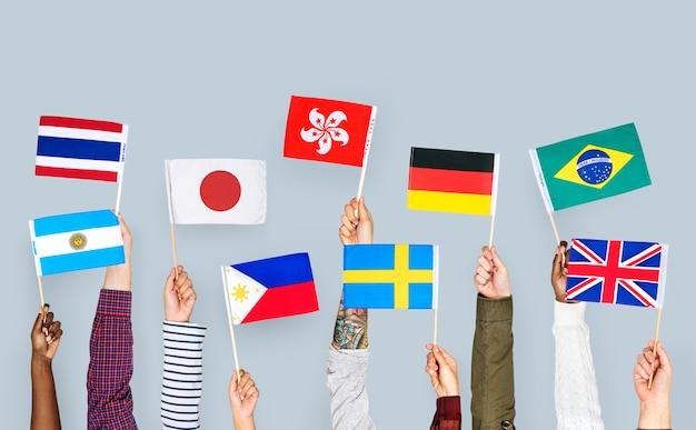 Hände, die internationale flaggen halten Premium Fotos