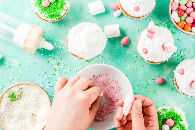 Hände, die ostern-kleine kuchen mit den häschenohren machen Premium Fotos