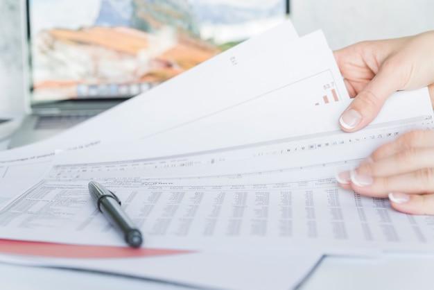 Hände, die papiere mit daten auf schreibtisch halten Kostenlose Fotos