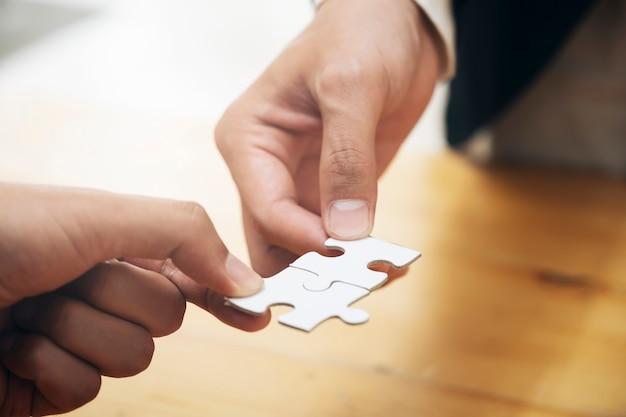 Hände, die puzzlen halten Premium Fotos