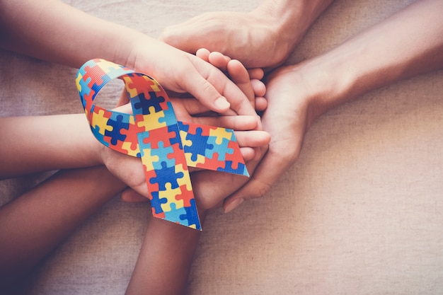 Hände, die puzzlespielband für autismusbewusstsein halten Premium Fotos