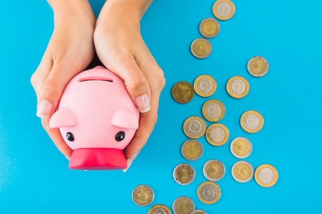 Hände, die sparschwein auf tabelle mit münzen halten Kostenlose Fotos