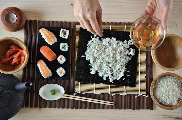 Hände, die sushi mit reis, lachsen und nori kochen Premium Fotos