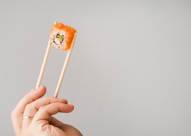 Hände, die sushirolle mit essstäbchenkopienraum halten Kostenlose Fotos