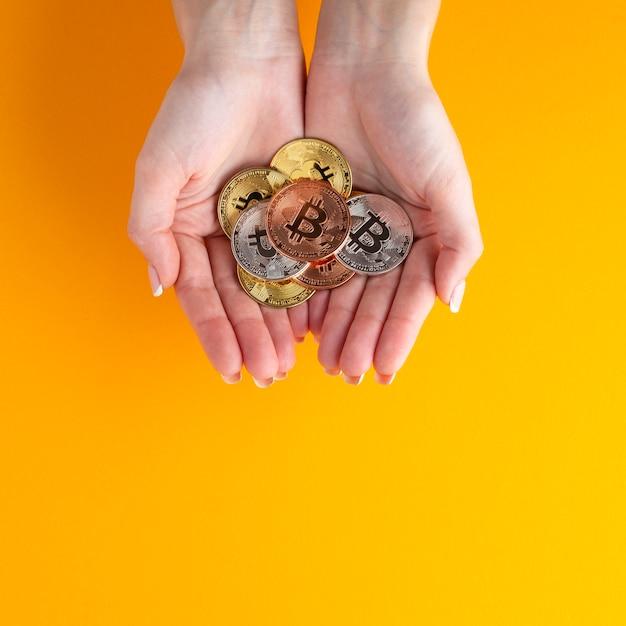 Hände, die unterschiedliches farbiges bitcoin halten Kostenlose Fotos