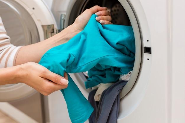 Hände, die waschmaschine der kleidung herausnehmen Kostenlose Fotos