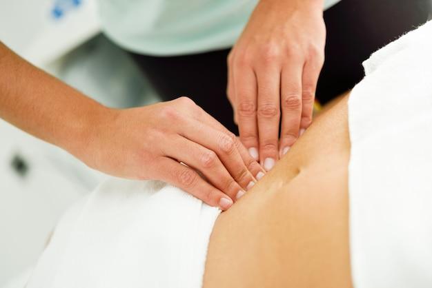 Hände, die weiblichen unterleib massieren therapeut, der druck auf bauch anwendet. Kostenlose Fotos