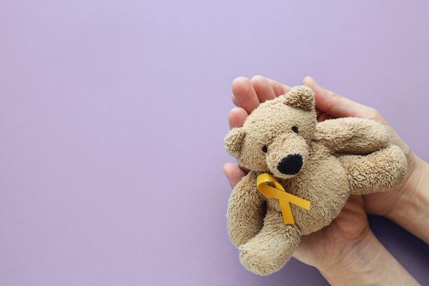 Hände, die weichen spielzeugbraunbären der kinder mit gelbgoldband auf purpurrotem hintergrund halten Premium Fotos