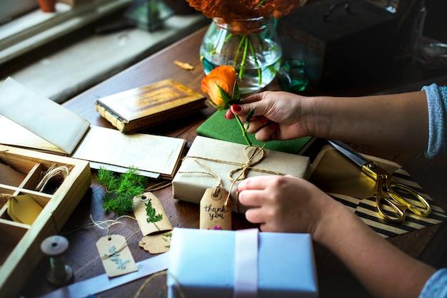 Hände diy geschenkbox auf holztisch einwickeln Premium Fotos