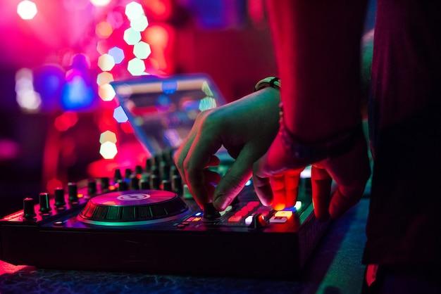 Hände dj, die musik auf musikprüfer an einer party spielen und mischen Premium Fotos