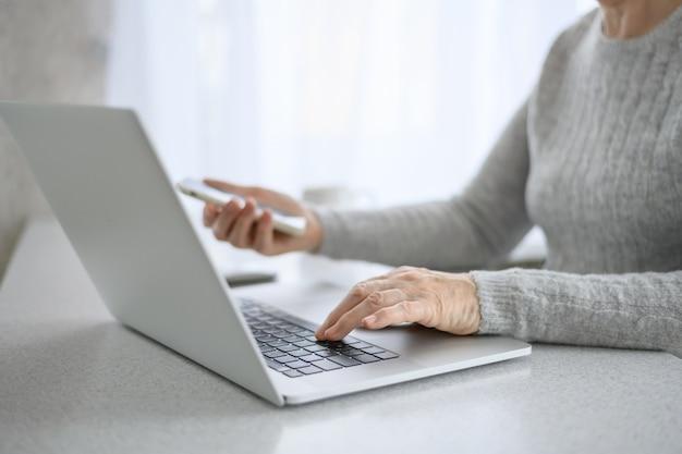 Hände einer älteren frau arbeiten an einem laptop mit telefon unter verwendung moderner technologie im täglichen leben. online einkaufen Premium Fotos