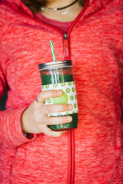 Hände einer frau, die ein grünes detox-kaltpresssaftglas hält Premium Fotos
