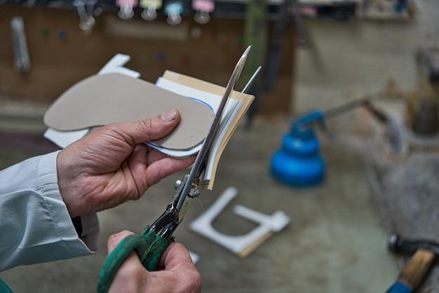 Hände einer orthopädischen handwerkerausschnittschere mit schaumschablonen und gummihandwerkern und personlaized für die füße. Premium Fotos