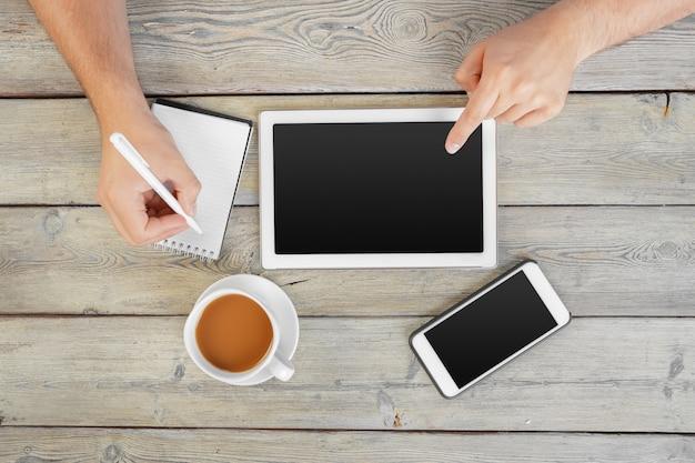 Hände eines mannes, der leeres tablettengerät über einer hölzernen arbeitsplatztabelle hält Premium Fotos