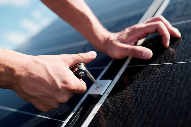 Hände eines professionellen technikers oder ingenieurs, der schrauben verwendet, während sonnenkollektoren auf dem dach des hauses installiert werden Premium Fotos