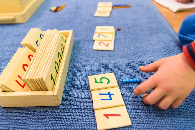 Hände eines studentenjungen, der hölzernes material in einer montessori-schule verwendet. Premium Fotos