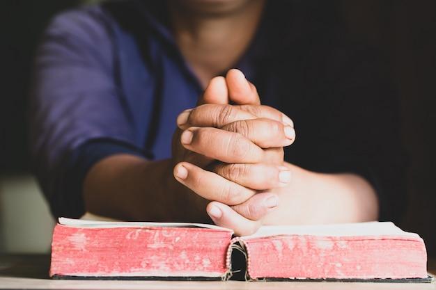 Hände falteten sich im gebet auf einer heiligen bibel im kirchenkonzept für glauben, spirtualität und religion Premium Fotos