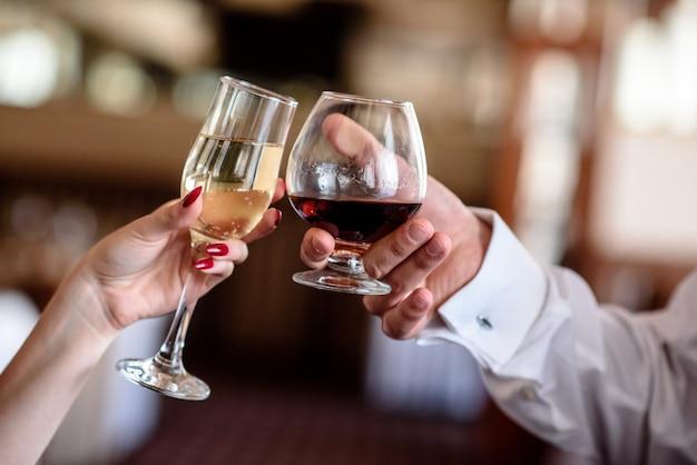 Hände halten die gläser brandy und champagner. Premium Fotos