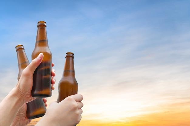 Hände halten drei bierflaschen. erfolg beim bier trinken. Premium Fotos