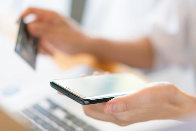 Hände halten eine kreditkarte mit laptop-computer und handy für online-shopping Kostenlose Fotos