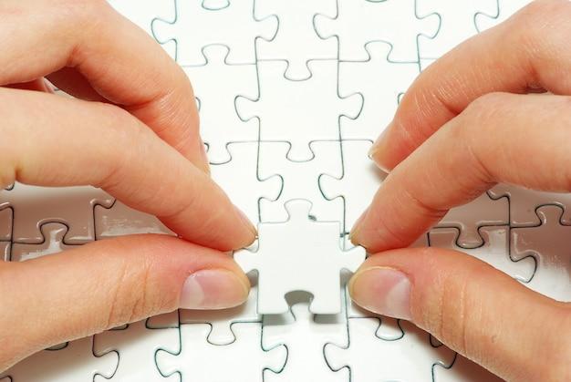 Hände halten leeres puzzleteil Premium Fotos