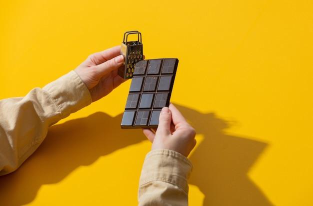 Hände halten schokolade und kleine reibe auf gelber oberfläche Premium Fotos