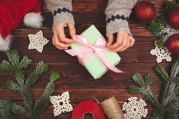 Hände in der strickjacke, die ein geschenk auf holztisch mit weihnachtsdekorationen hält Premium Fotos
