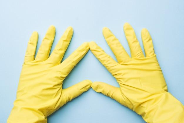Hände in gelben handschuhen für das säubern auf blauer oberfläche Premium Fotos