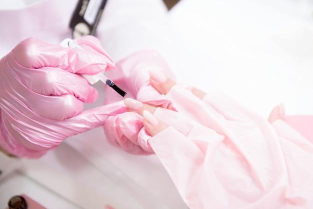 Hände in handschuhen kümmern sich um handnägel. maniküre-schönheitssalon. Premium Fotos
