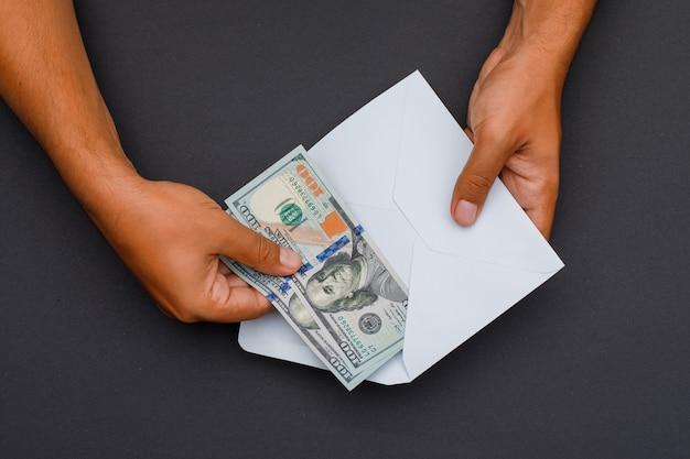 Hände legen banknoten in umschlag. Kostenlose Fotos