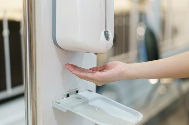 Hände mit automatischer desinfektionsflüssigkeitssprühmaschine, berührungslosem spender. Premium Fotos