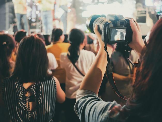 Hände mit der digitalkamera, die foto in stadium des musikkonzerts macht Premium Fotos