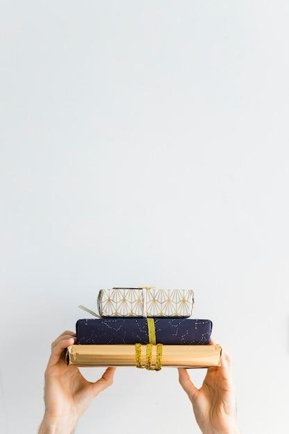 Hände mit geschenkboxen in sweetie-papieren Kostenlose Fotos