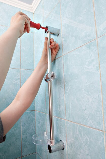 Hände mit schraubendreher an wand duschkopf gleitschiene bar mit seifenschale befestigt. Premium Fotos