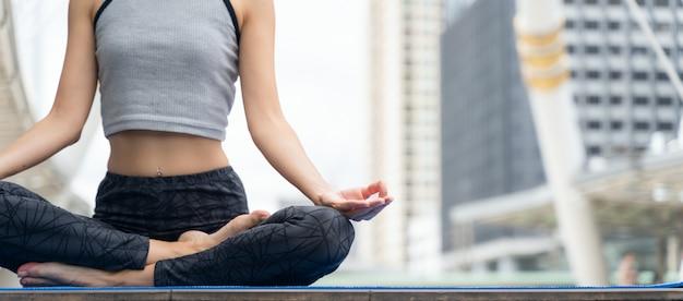 Hände schließen. frau tun das yoga, das in der stadt im freien ist. frau, die lebenswichtig und meditation für eignungslebensstil am freien in der stadt ausübt. Premium Fotos