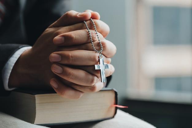 Hände schließen. geschäftsmänner, die jesus-kreuz halten und hände und bibel in der front beten Premium Fotos